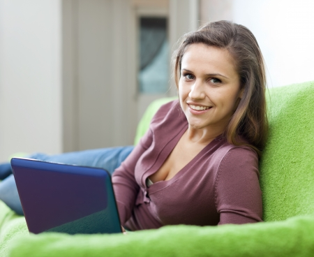 Young woman using netbook on sofa  in home photo