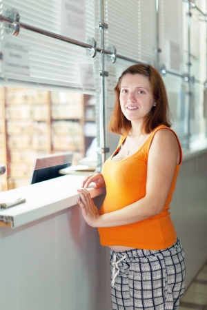 gravida: Pregnant woman waiting  for patients records in clinic reception desk