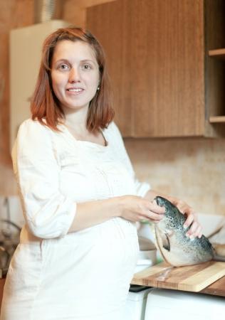 gravida: pregnant woman cooks salmon in the kitchen  Stock Photo