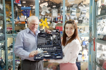 mature man buys  automotive  tool set in  auto parts store photo