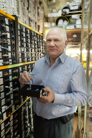 mature man chooses hardware in  auto spare parts store Stock Photo - 17335504