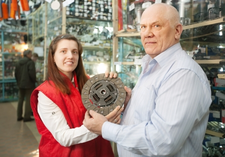 mature man buys engine clutch in auto parts store photo