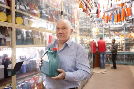 motor oil: Mature man holds  motor oil in  auto  parts store