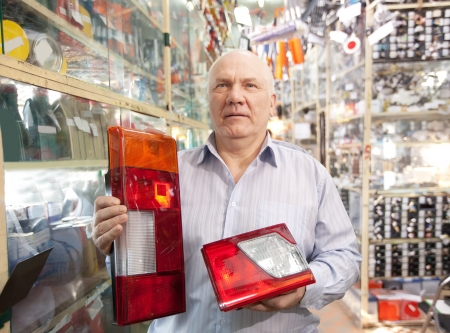 mature man holds  automotive  headlight  in  auto parts store photo