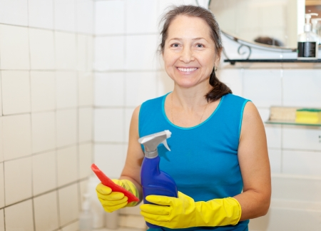Smiling mature woman cleans bathroom with rug and cleaner at home photo