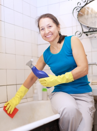Smiling mature woman cleans bathtub in bathroom at her home photo