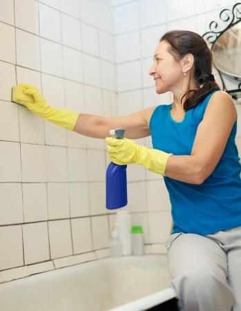 mujer limpiando: Sonriente mujer madura limpia azulejo con una esponja y limpiador en el ba�o