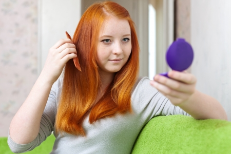 red-haired girl combing  hair in home interior photo