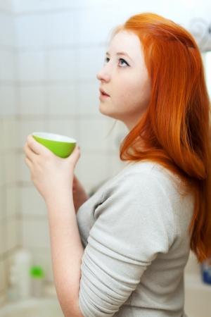 sicken: Teen girl gargling throat in her bathroom at home