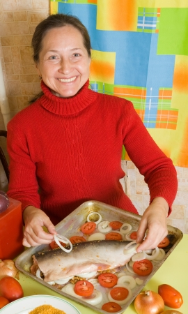 tomatto:  Woman cooking  salmon fish on  roasting pan