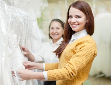 bridal salon: Two women chooses white dress at shop of wedding fashion Stock Photo