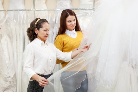 Shop assistant  helps the bride in choosing bridal outfit at shop of wedding fashion  Focus on mature Stock Photo - 17381037