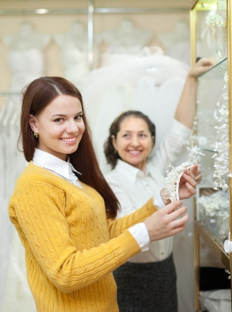women  chooses bridal accessories in  boutique photo
