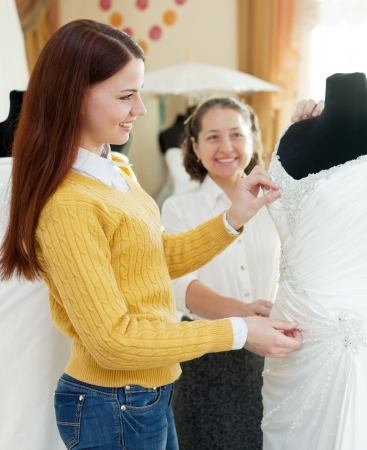 Happy mother  with daughter chooses bridal gown at shop of wedding fashion  Focus on bride photo
