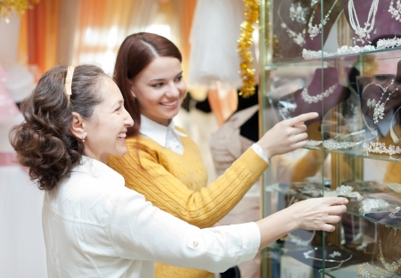 neckless: Smiling women  chooses bridal accessories at store of wedding fashion Stock Photo