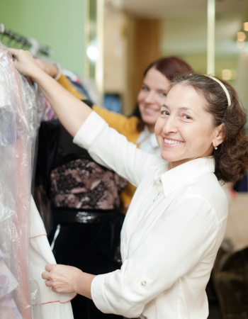women chooses  dress at shop of fashionable clothes photo