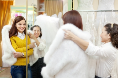 Female shop consultant helps bride chooses fur cape at shop of wedding fashion  Focus on reflection photo