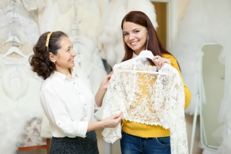 bride chooses bridal clothes at shop of wedding fashion  Friendly consultant helps her photo