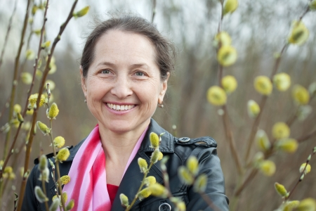 portrait of mature woman in spring pussywillow plant photo