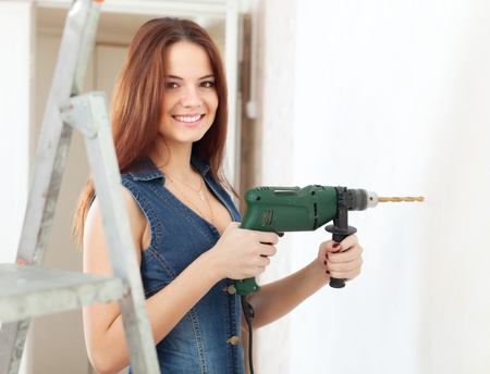 Happy girl in overalls drills hole in the wall with drill  at home photo