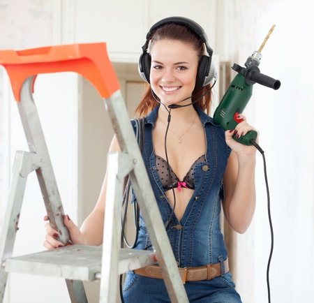Sexy woman in headphones with drill on stepladder  photo