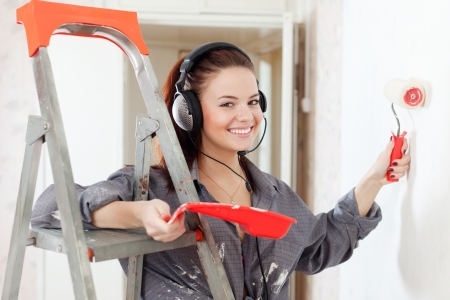 scaling ladder: Happy young woman in headphones paints wall with roller Stock Photo