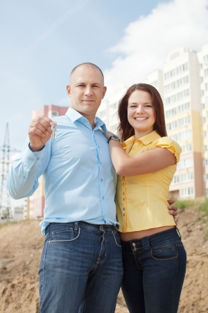 Outdoor portrait of   happy couple against real estate photo