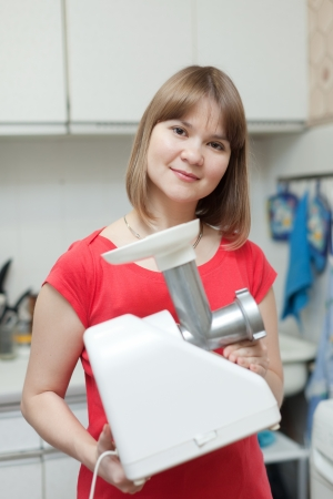 eastward: Woman with electric mincing-machine in kitchen