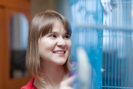 eastward: Smiling woman at the cage with pets at home Stock Photo