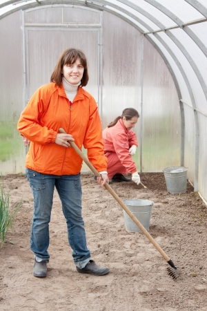 Happy women works at hothouse in spring photo