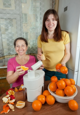 citrus family:  Two women  making fresh orange juice in home kitchen  Stock Photo