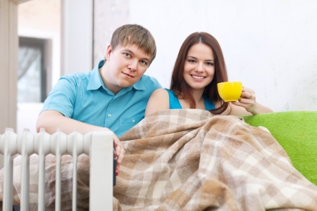 heat register: Couple  relaxing at home near oil heater