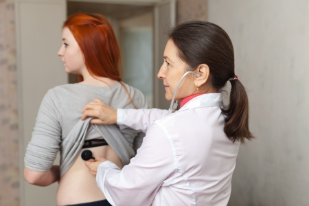 auscultoscope: Serious mature female doctor examining young girl with stethoscope