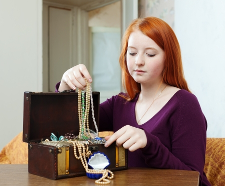 ruby house: portrait of teen girl chooses jewelry in treasure chest at home Stock Photo