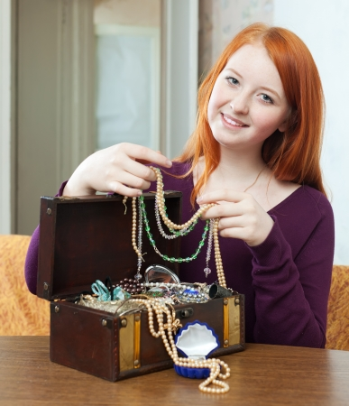 portrait of  red-headed girl looks jewelry in treasure chest at home interior Stock Photo