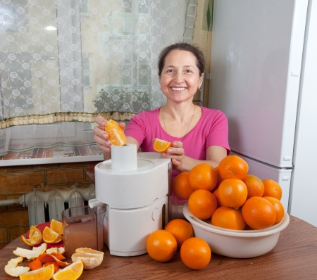 smiling mature woman adding orange to juicer in her kitchen photo