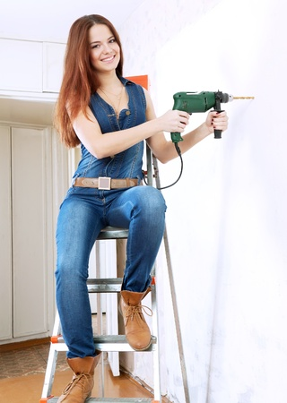 woman in overalls with drill makes repairs in home photo