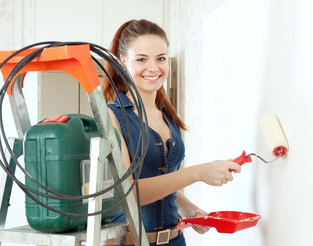 scaling ladder: Happy woman in deniums paints wall with roller at home