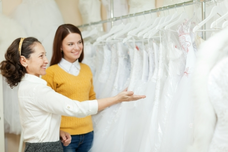 Shop assistant  helps the bride in choosing  dress at shop Stock Photo - 17467445