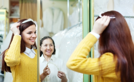 pretty bride chooses bridal accessories at shop of wedding fashion  Consultant helps her photo