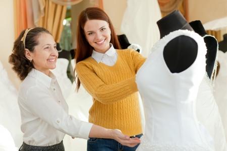 bridal gown: Dependienta madura con la ni�a elige vestido de novia en la tienda de moda nupcial Foto de archivo