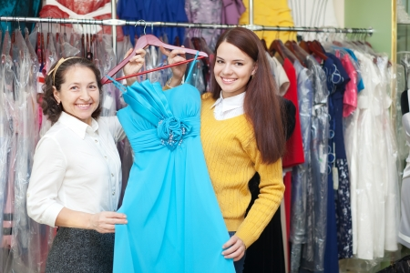 women chooses blue evening gown at shop of fashionable clothes photo