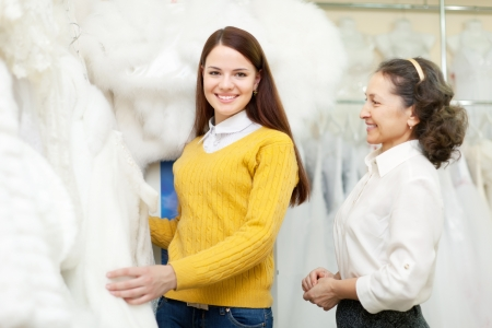 capote:  shop consultant helps bride chooses bridal clothes at shop of wedding fashion  Focus on girl Stock Photo
