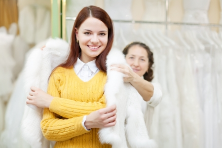 Female shop consultant helps girl chooses fur cape at shop of wedding fashion  Focus on bride photo