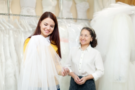 Girl chooses bridal veil at shop of wedding fashion  Consultant helps her photo
