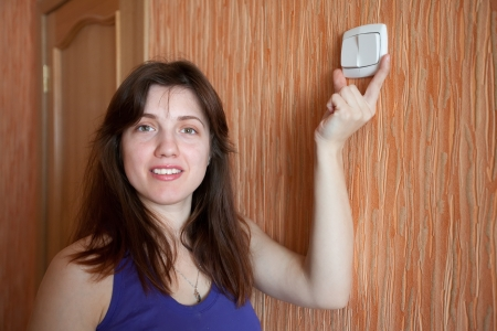 Young woman with light-switch in home Stock Photo - 17493050