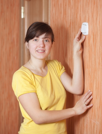 turns of the year: Young woman turning off the light-switch in home