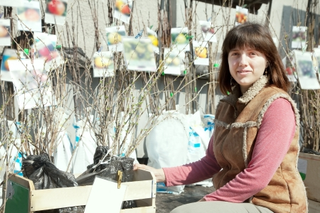 Female gardener chooses sprouts at market photo