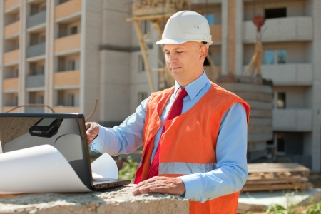 Portrait of white-collar worker wearing protective helmet works on the building site Stock Photo - 17493404