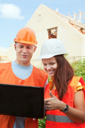 two happy builders in hardhat works on the building site Stock Photo